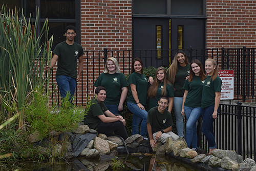 Wide shot of Environmental students outside near the pond