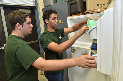 Two environmental boys grabbing food from a fridge
