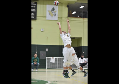 Wide shot of the Boys Varsity Volleyball team with a player jumping in the air