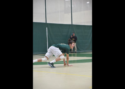 Wide shot of a boy volleyball player crouched on the floor
