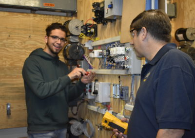 Electrical student showing teacher work