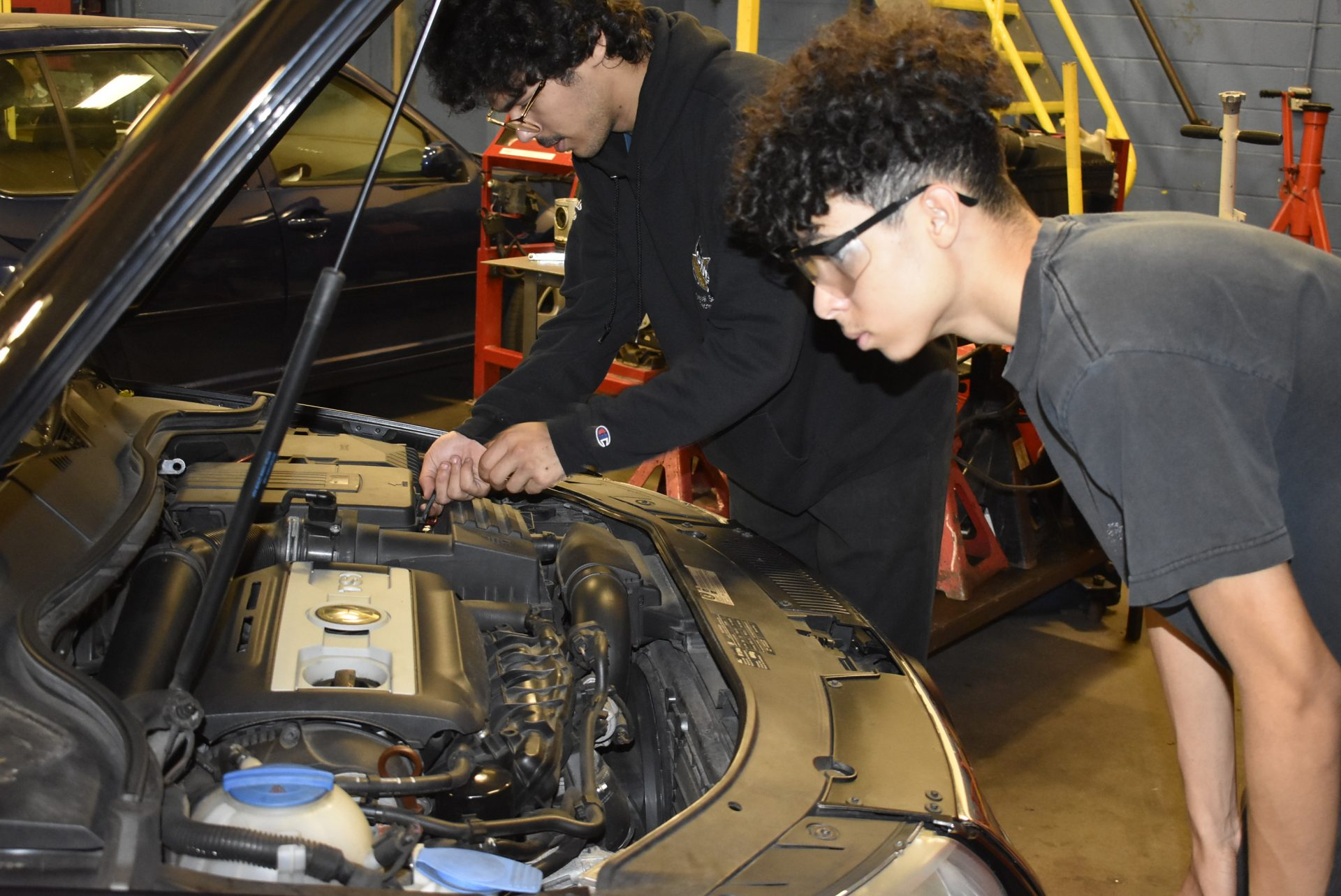 Diesel students working under a car's hood