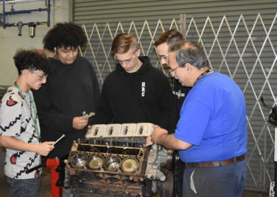 Automotive students working with their teacher on a car engine