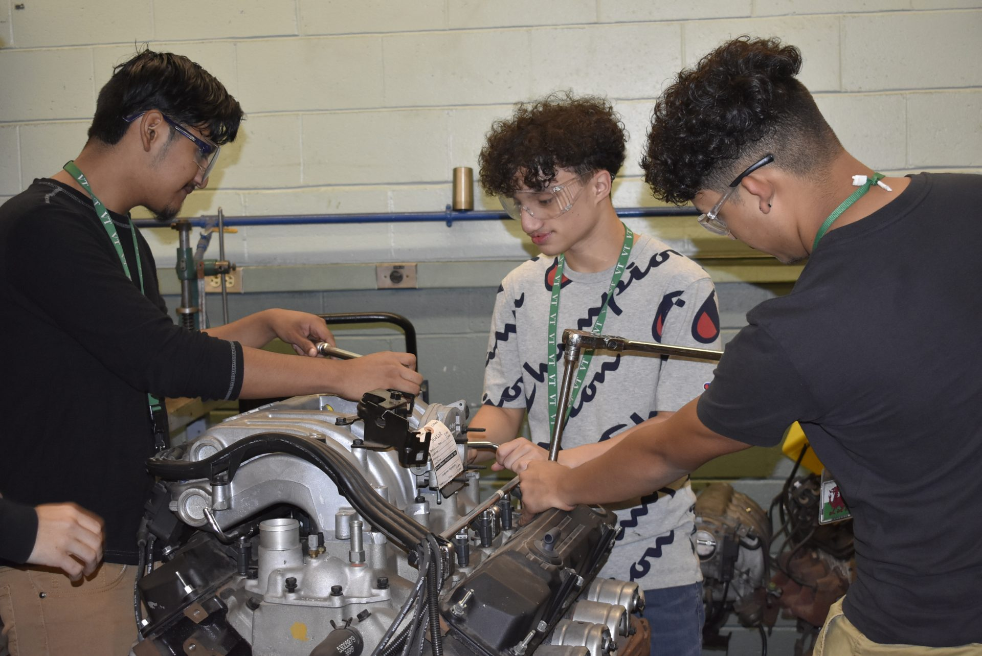 Automotive students working on car parts