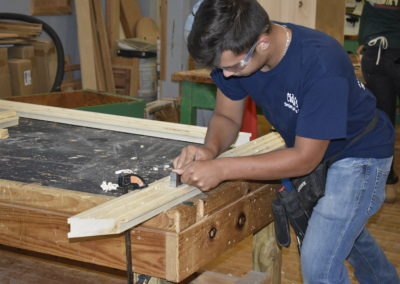 Carpentry student shaving wood