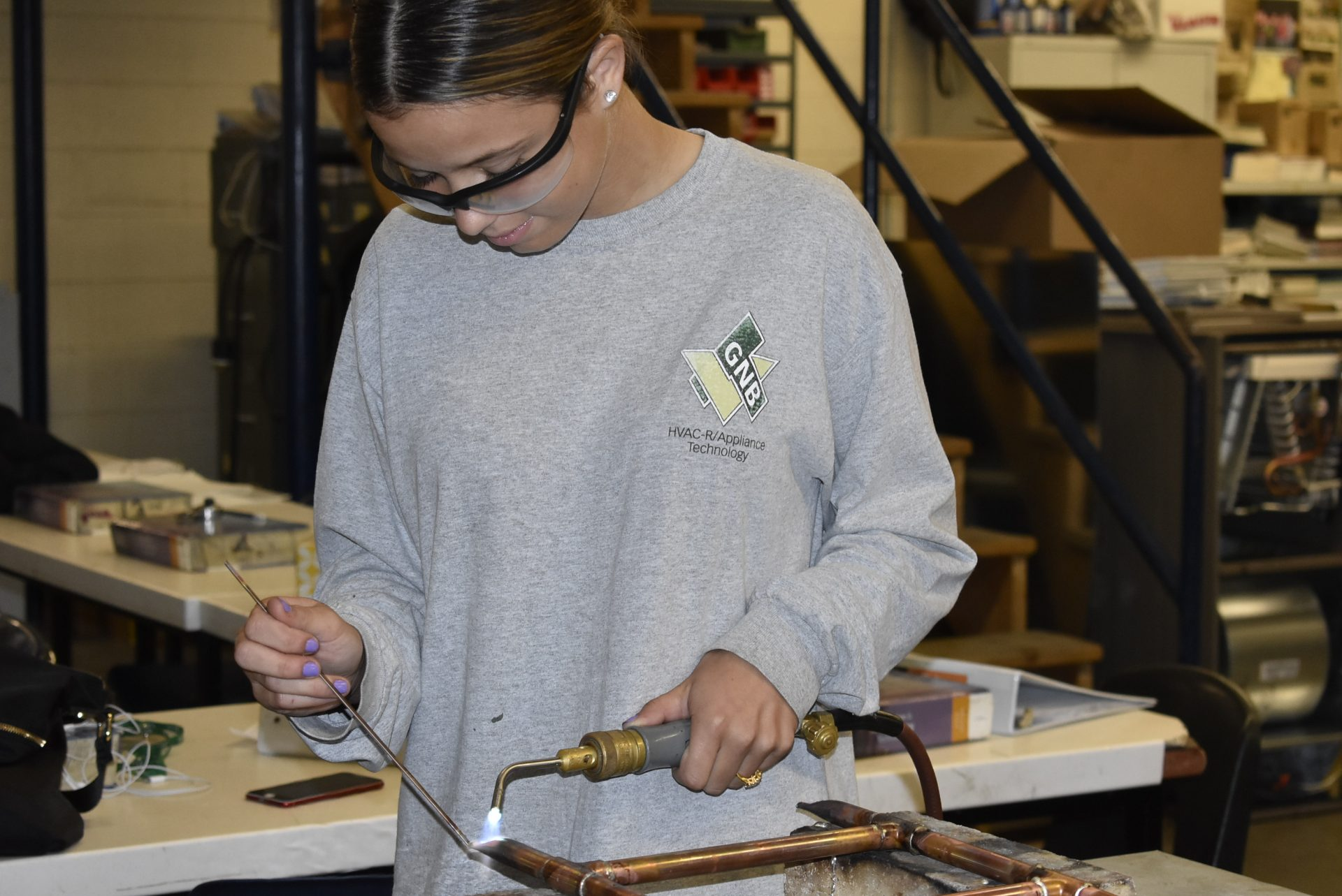 Senior in HVAC working with blow torch