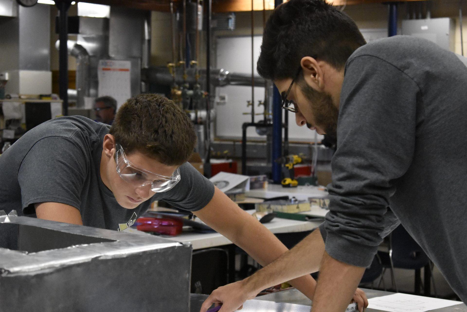 HVAC students working with a Metal Sheet