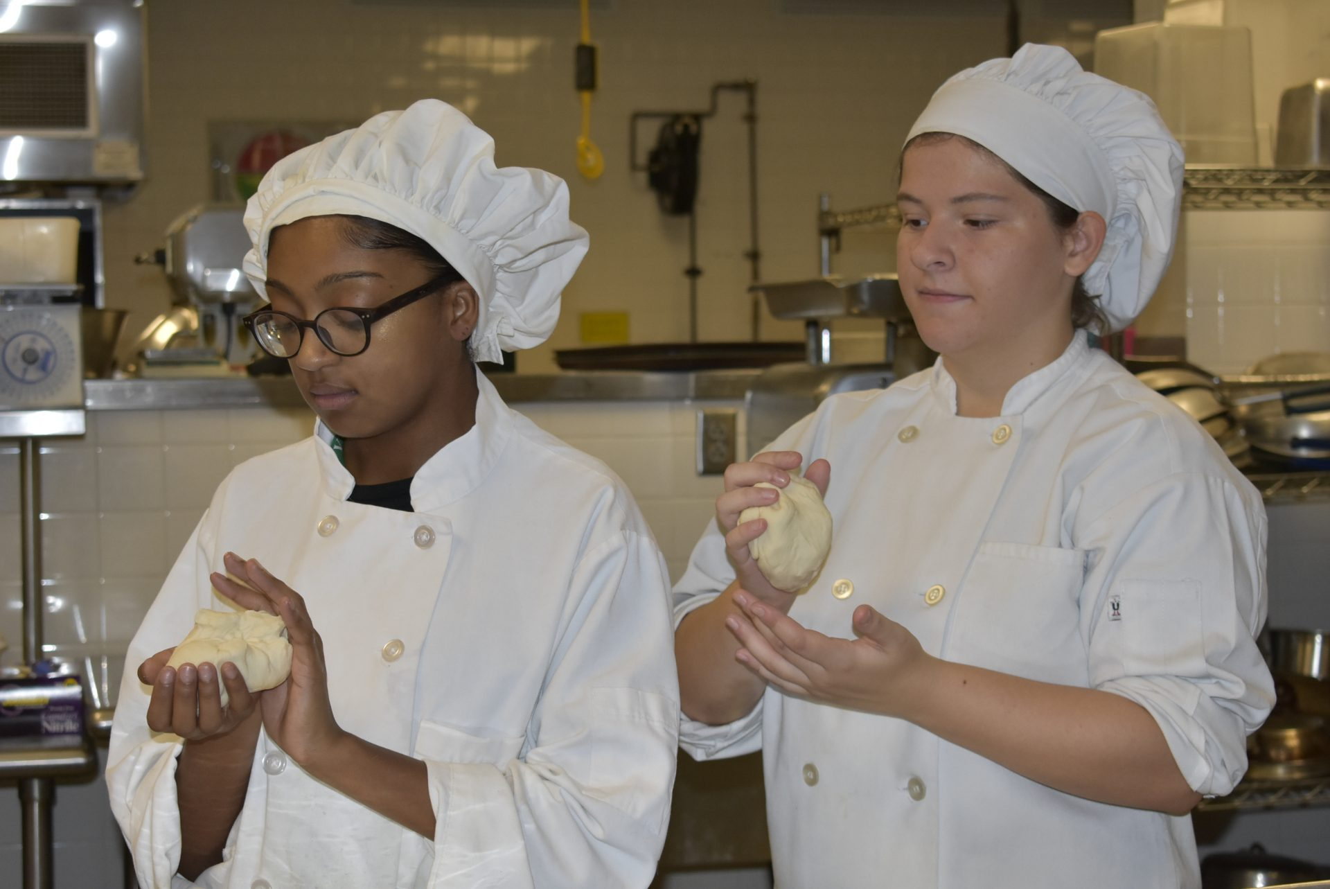 Culinary students kneading dough