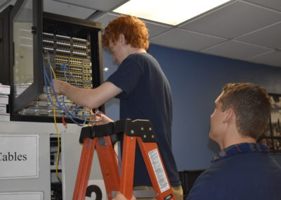 Informational technology student holding a ladder for another student