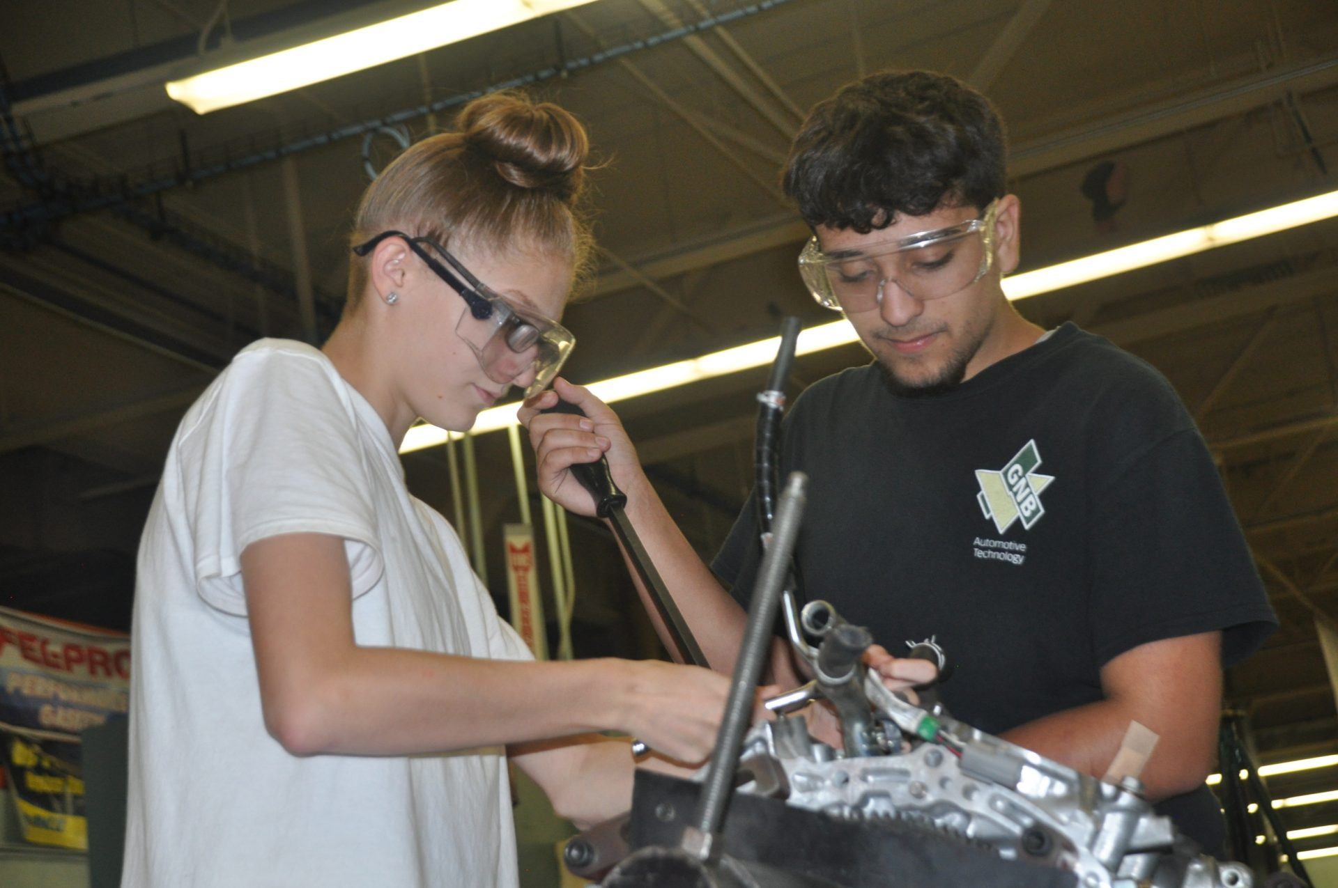 Automotive students working together on a engine