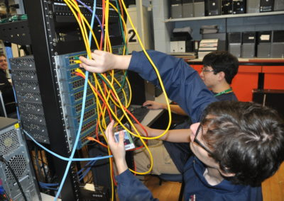 Informational technology student plugging wires in