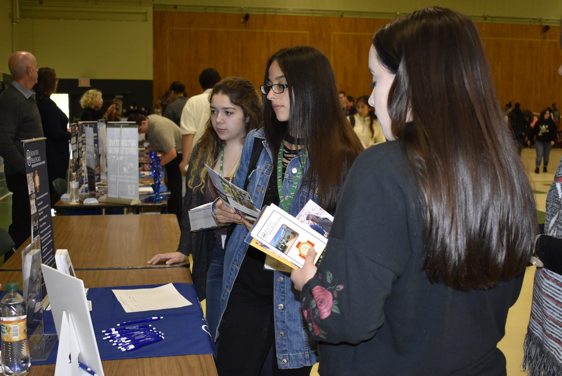 Students Looking At A College's Mini-Poster