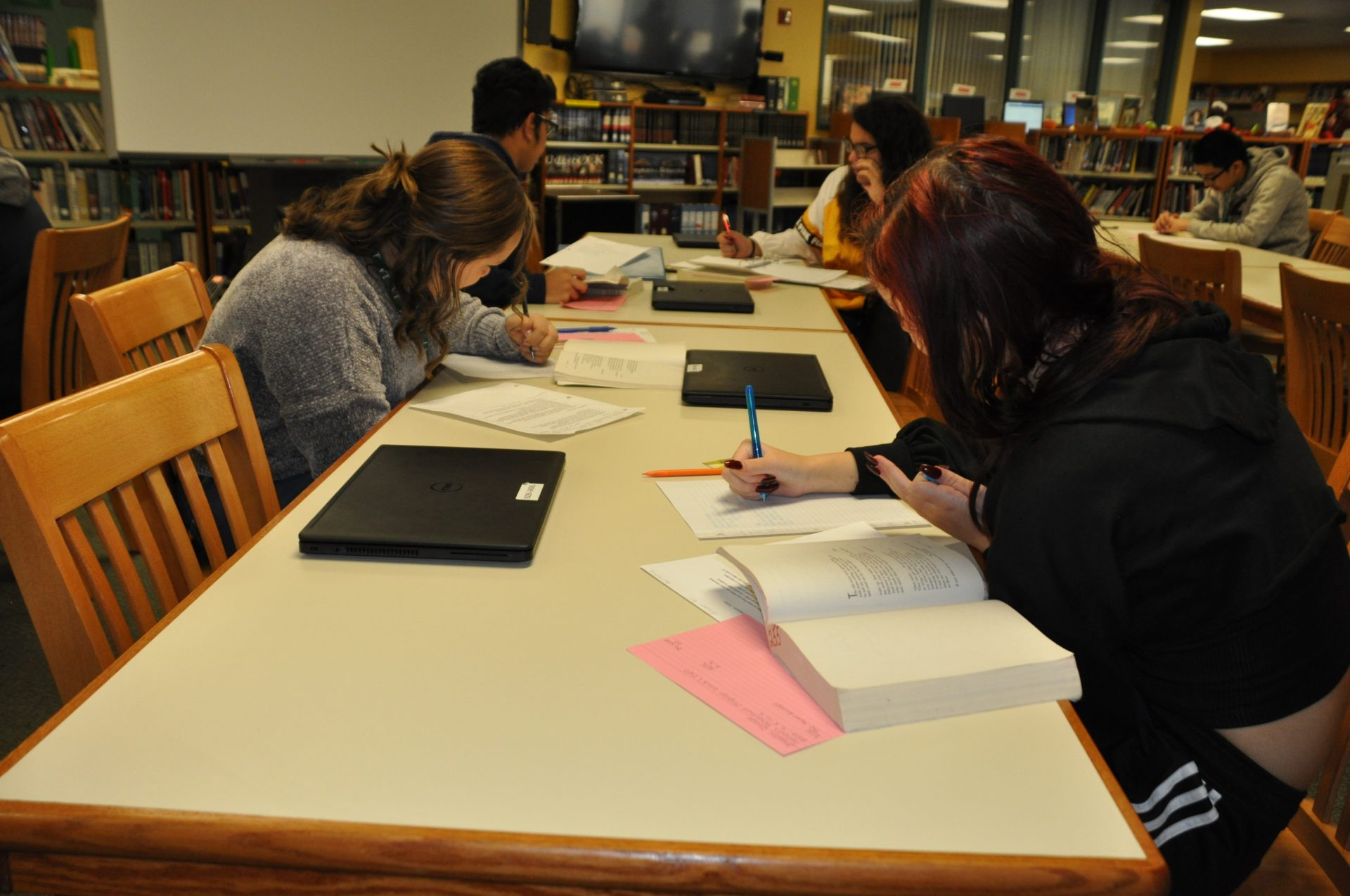 Students writing in the library