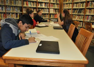Students writing and conversing in the library