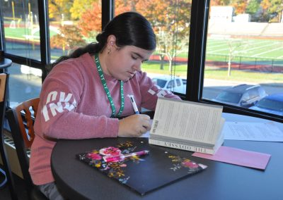 Student writing in the library