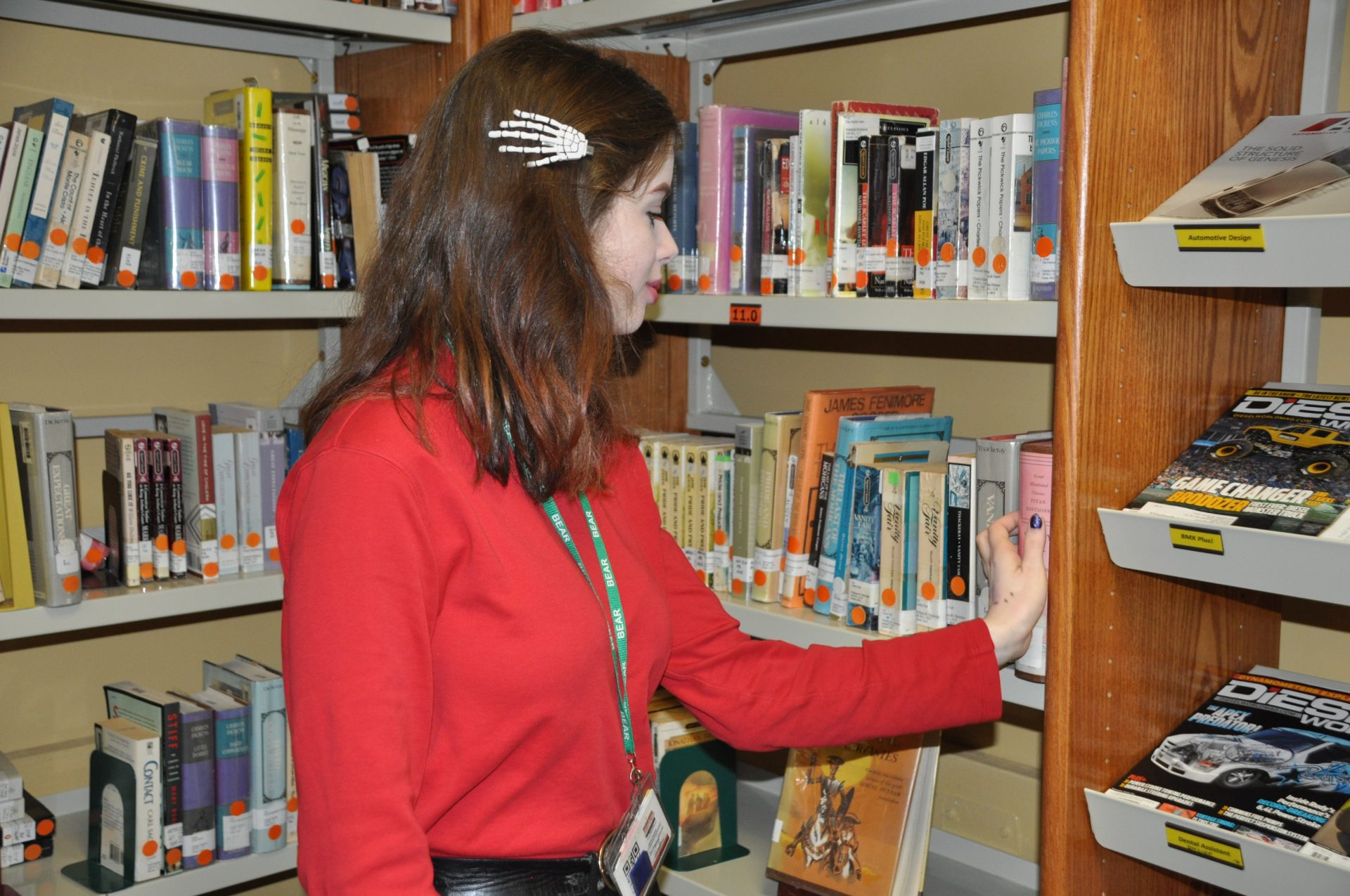 Student looking at a book in the library