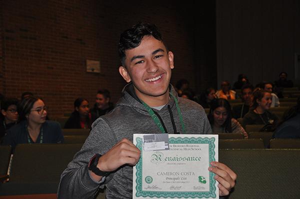 Student holding up renaissance award