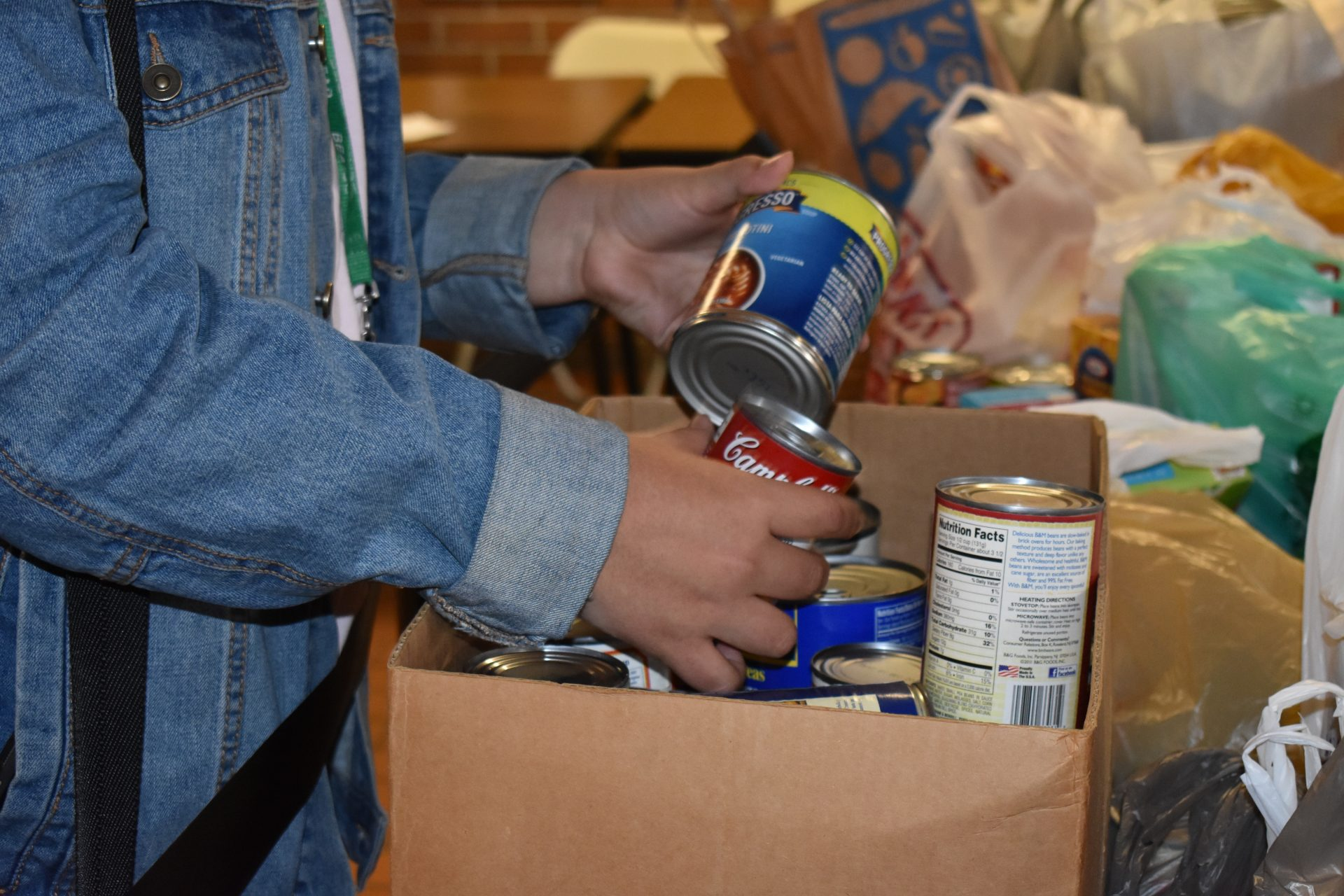 Student Holding Cans