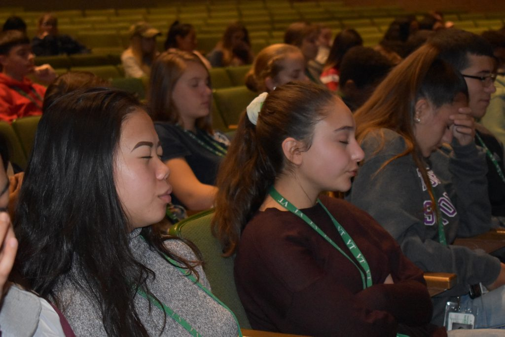 students with eyes closed in the audience