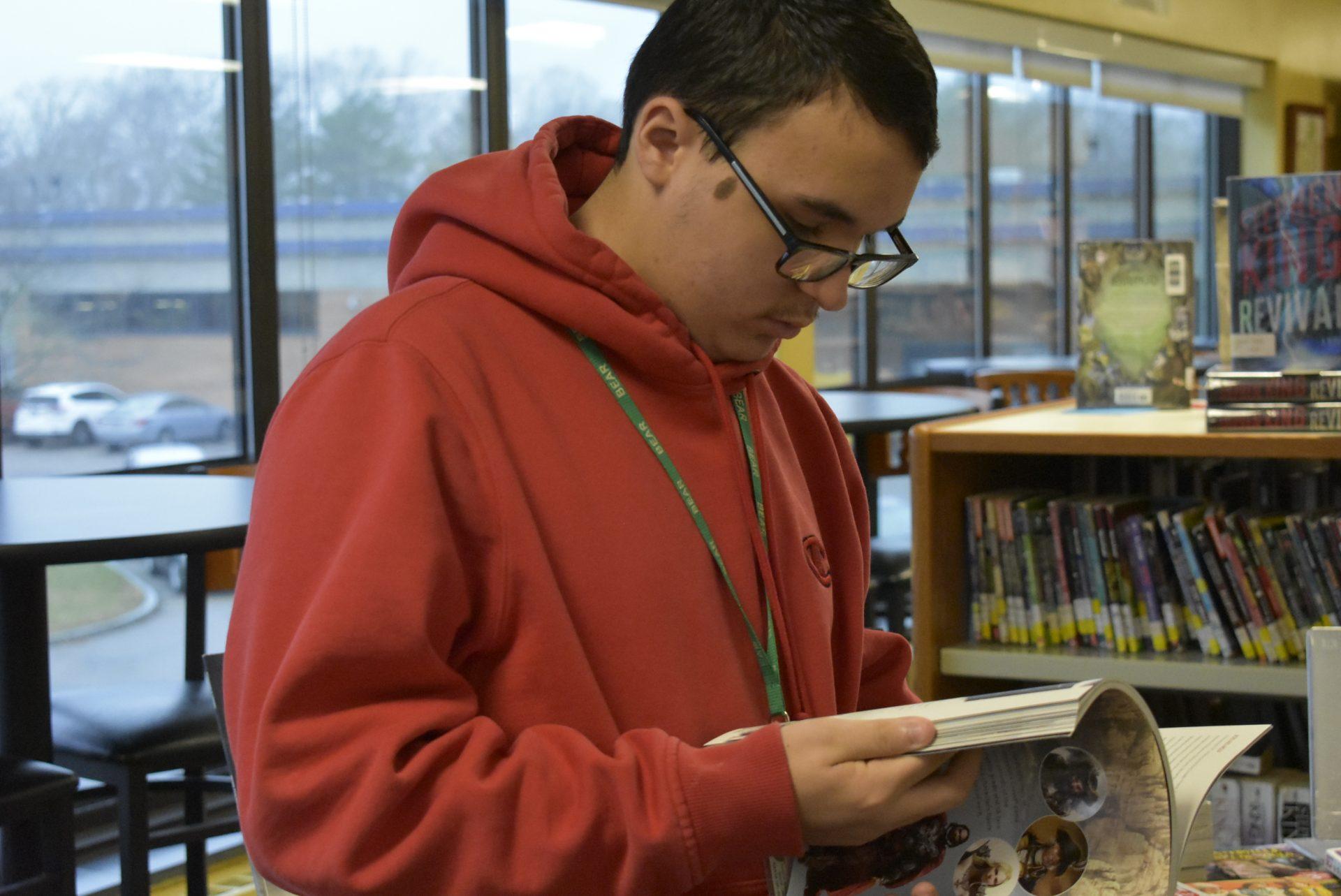 Student in red hoodie looking through book