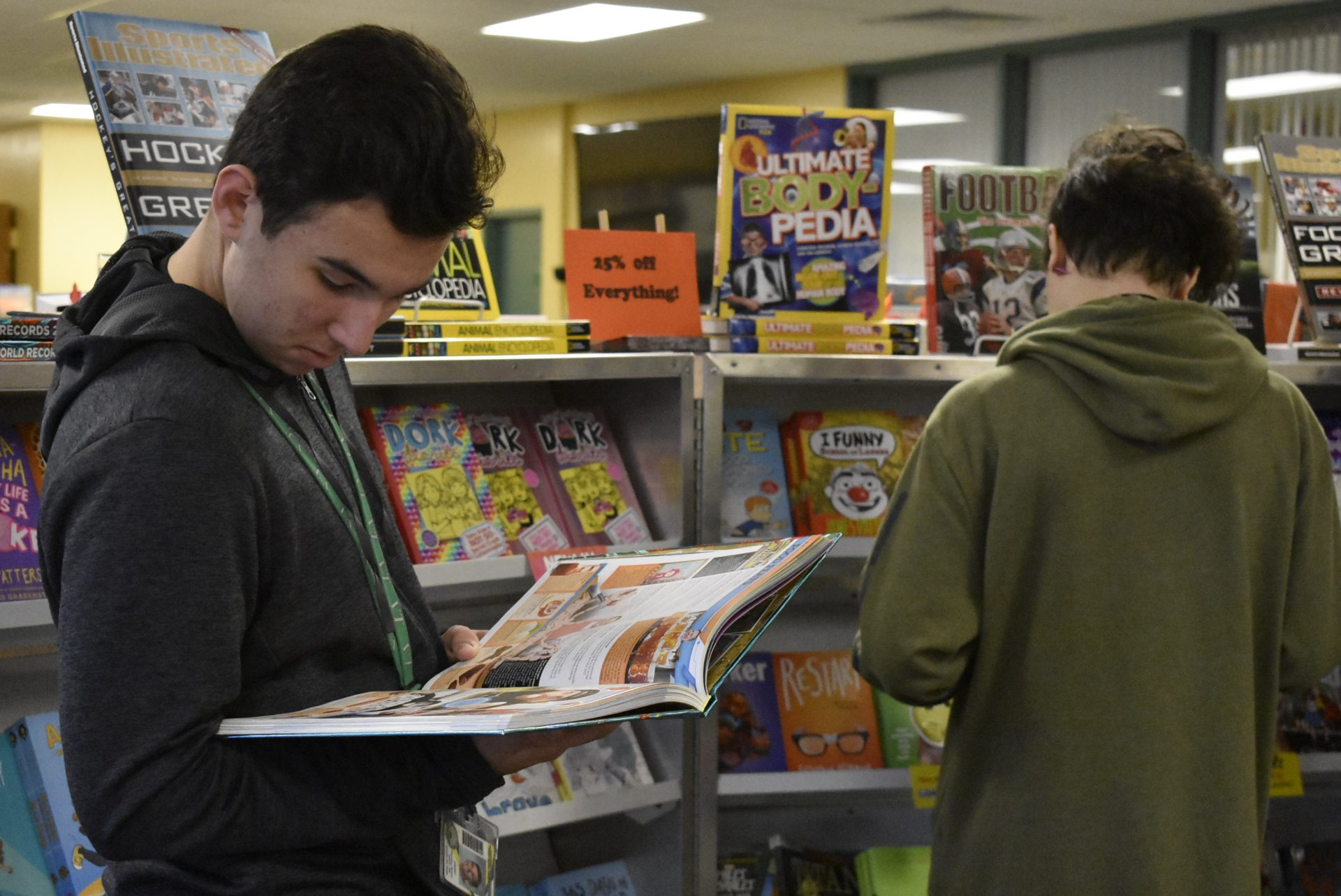 Two Students looking at books with bookshelf in background