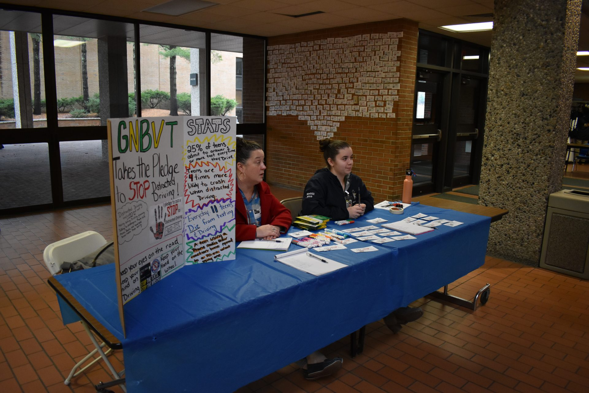 student and teacher at pledge desk waiting for signatures
