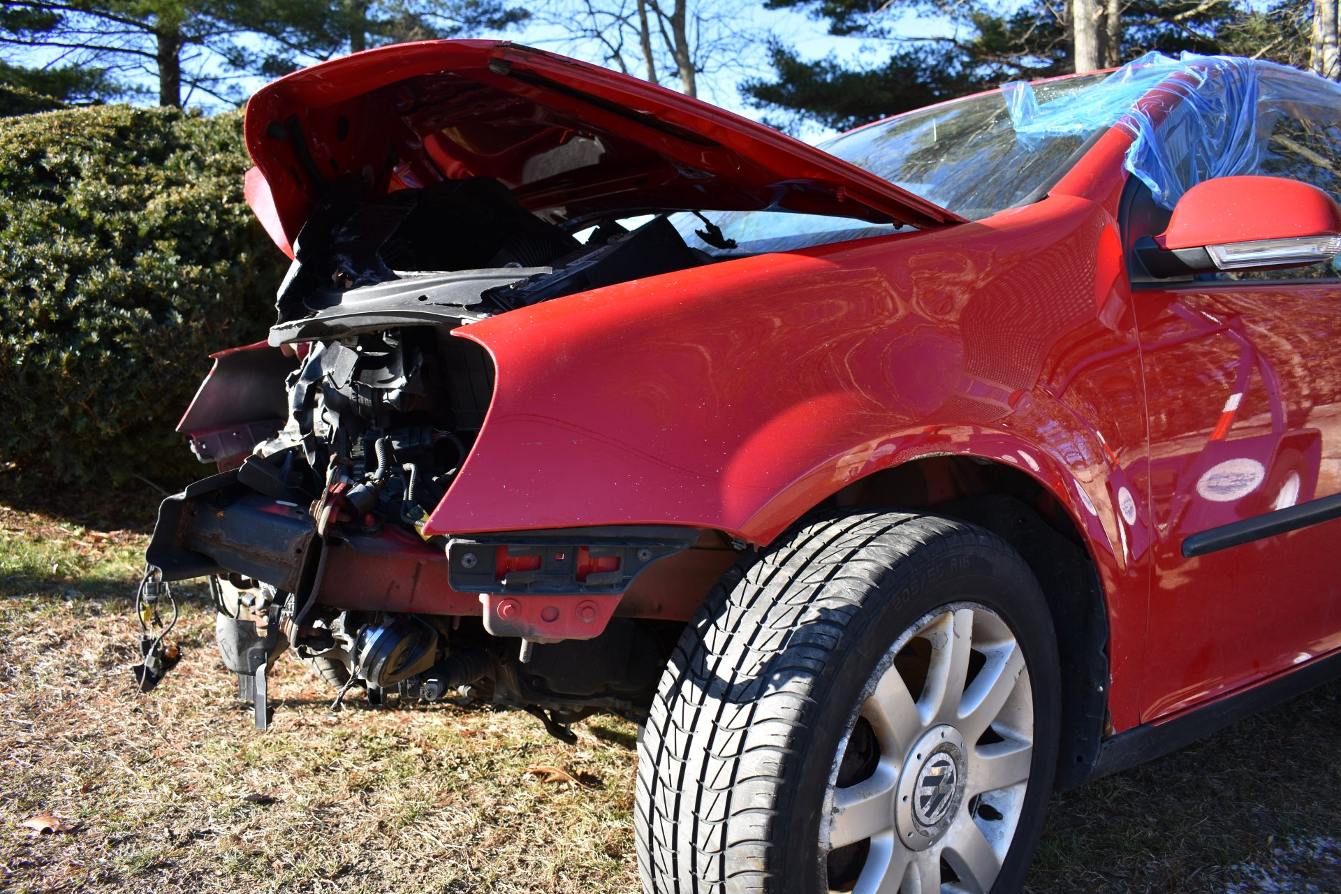 side close up of totaled red Volkswagen