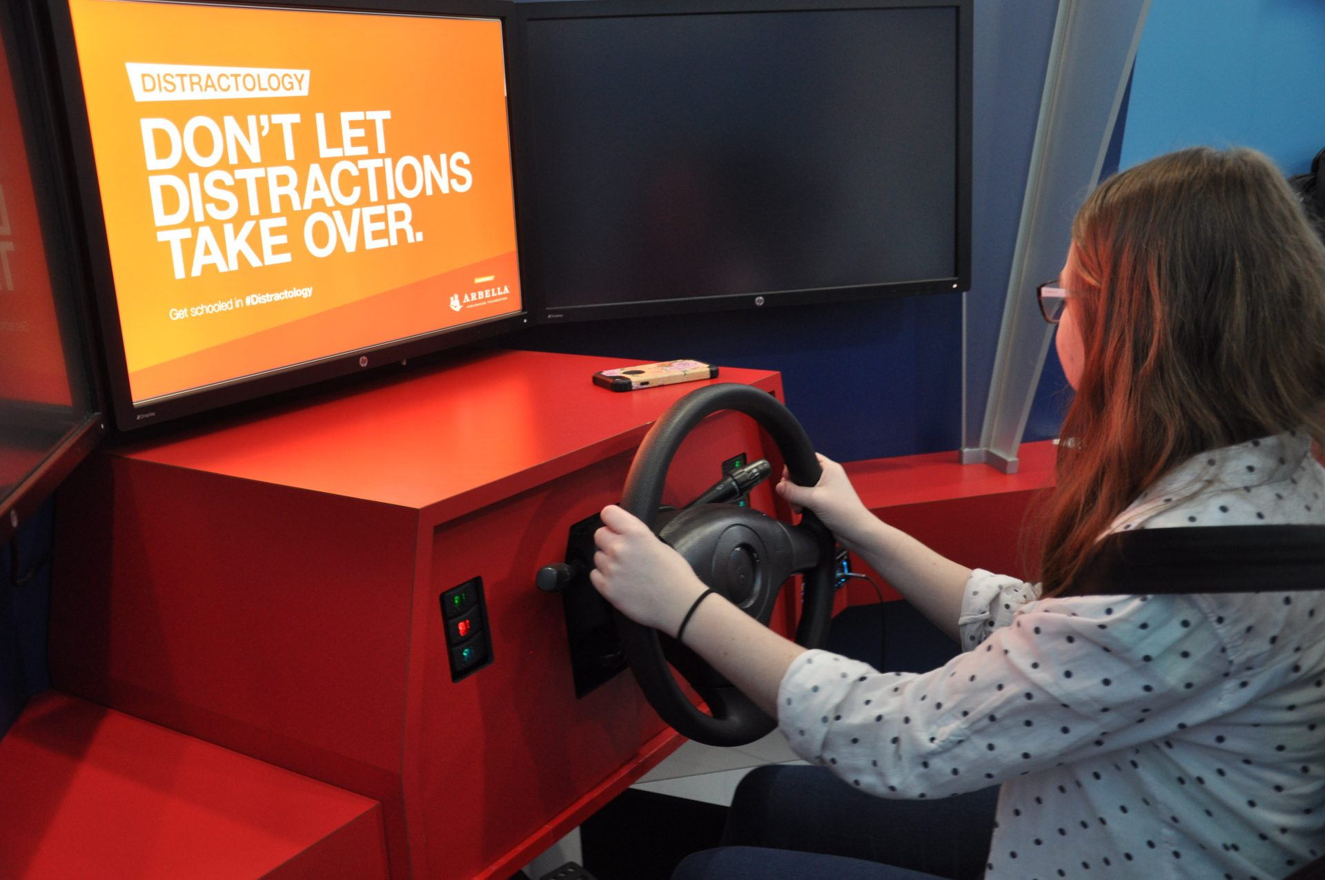Student seated in Distractology driver's seat