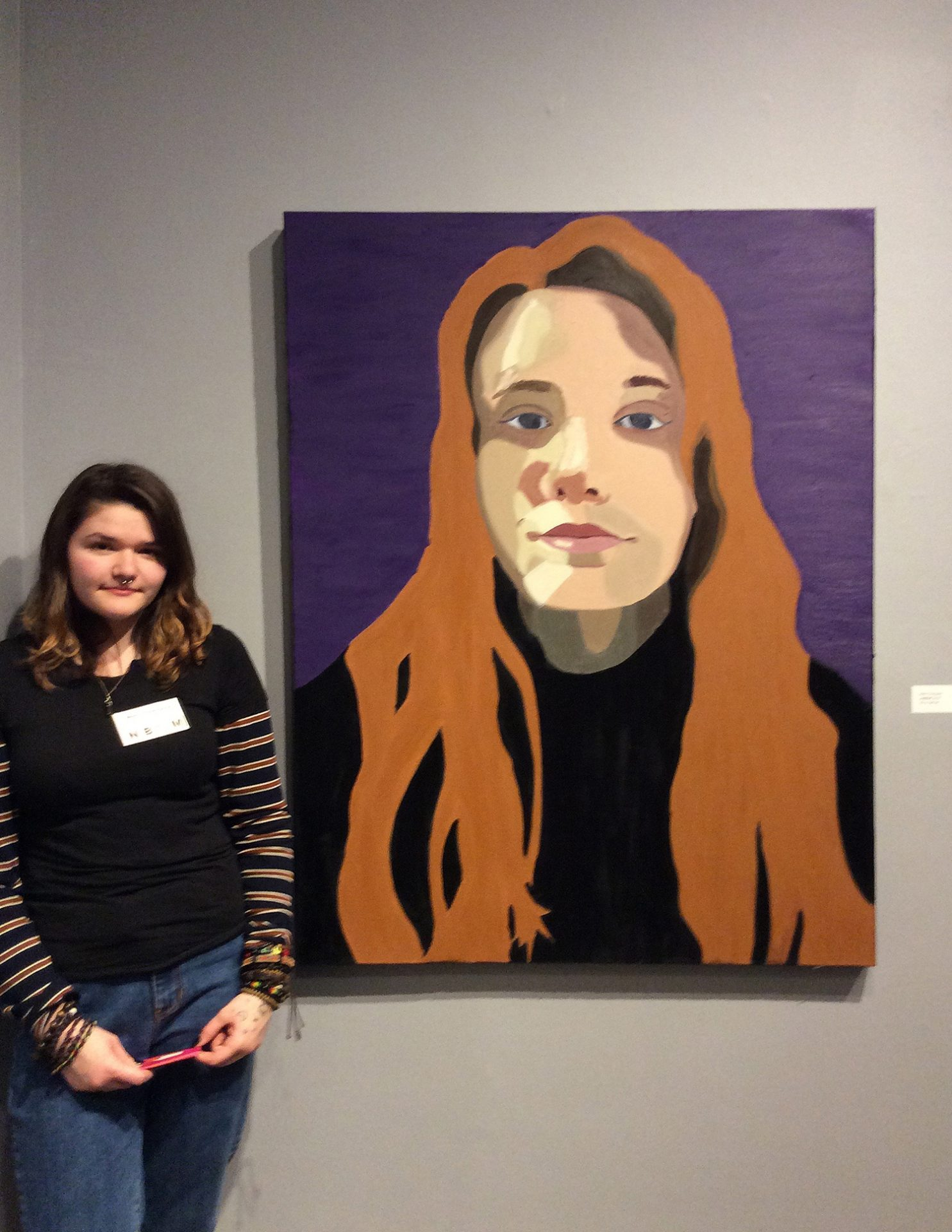 Teen Artist Internship student standing near their artwork