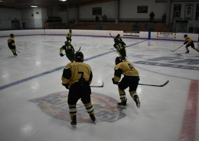 two voc players rushing to get to puck