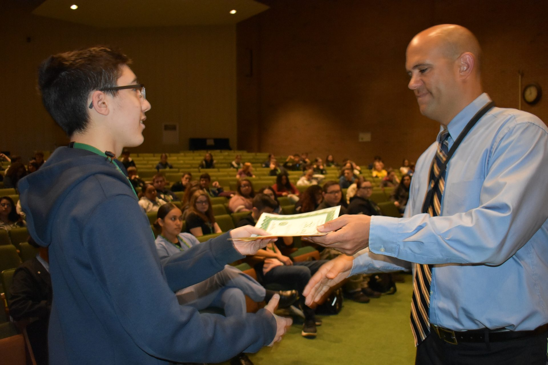 Renaissance Awards student receives an award from Mr. Viera