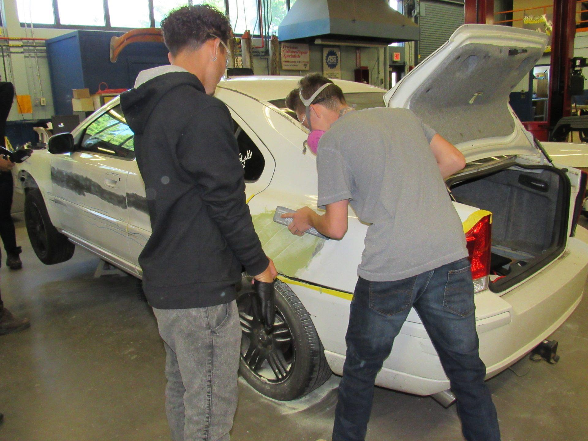 Collision students sanding car