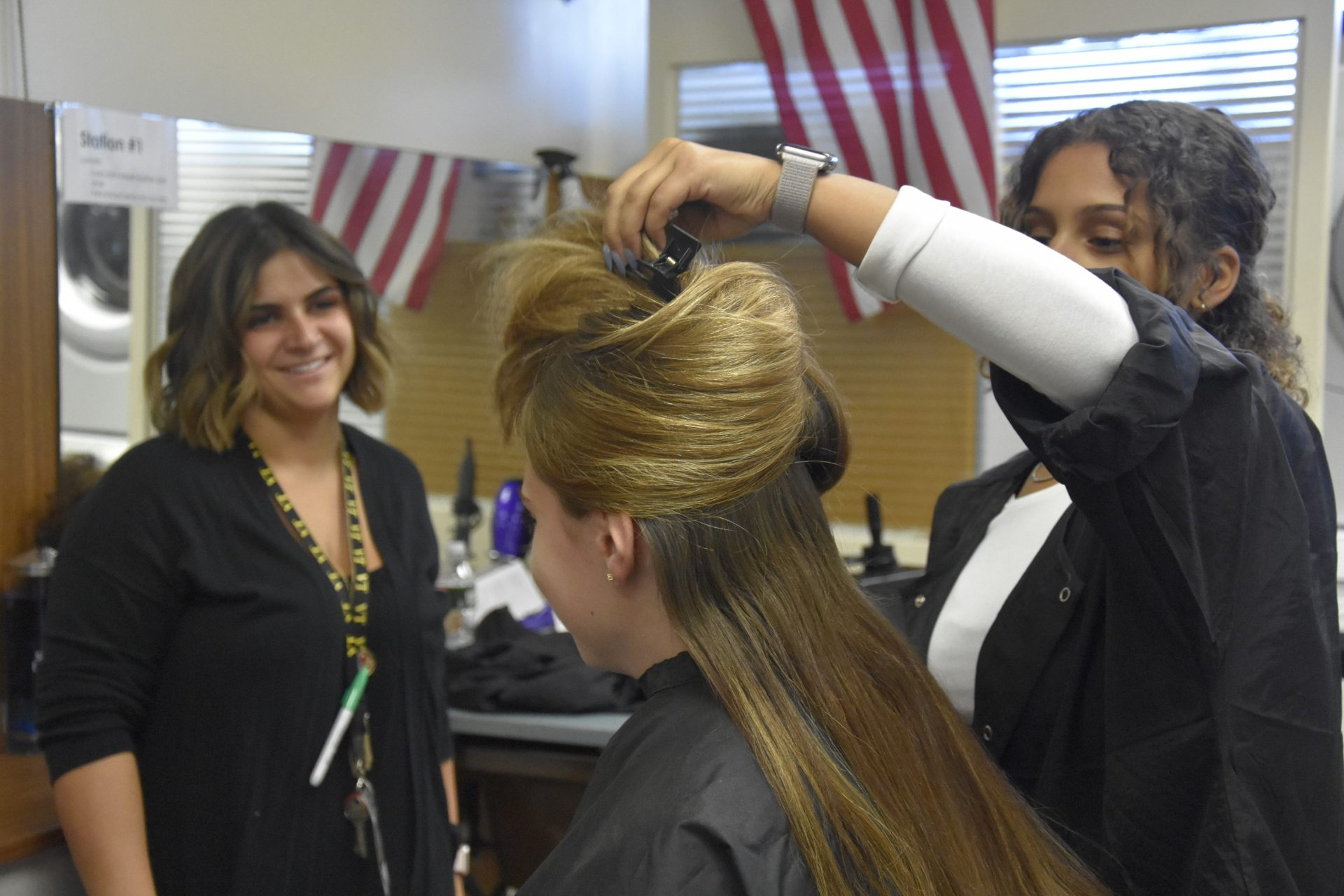 Cosmo students doing hair while teacher observes