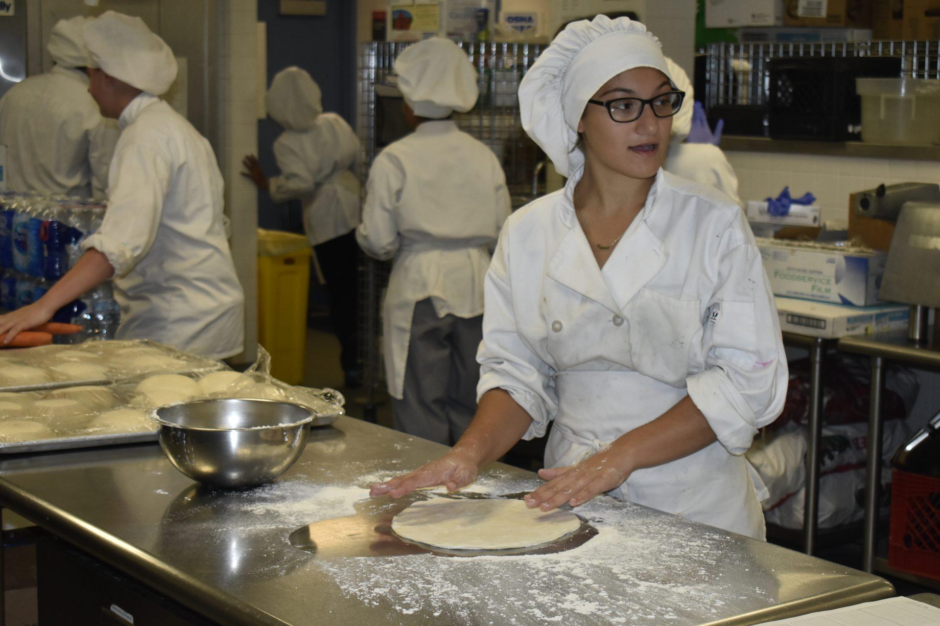 Cu student rolling dough