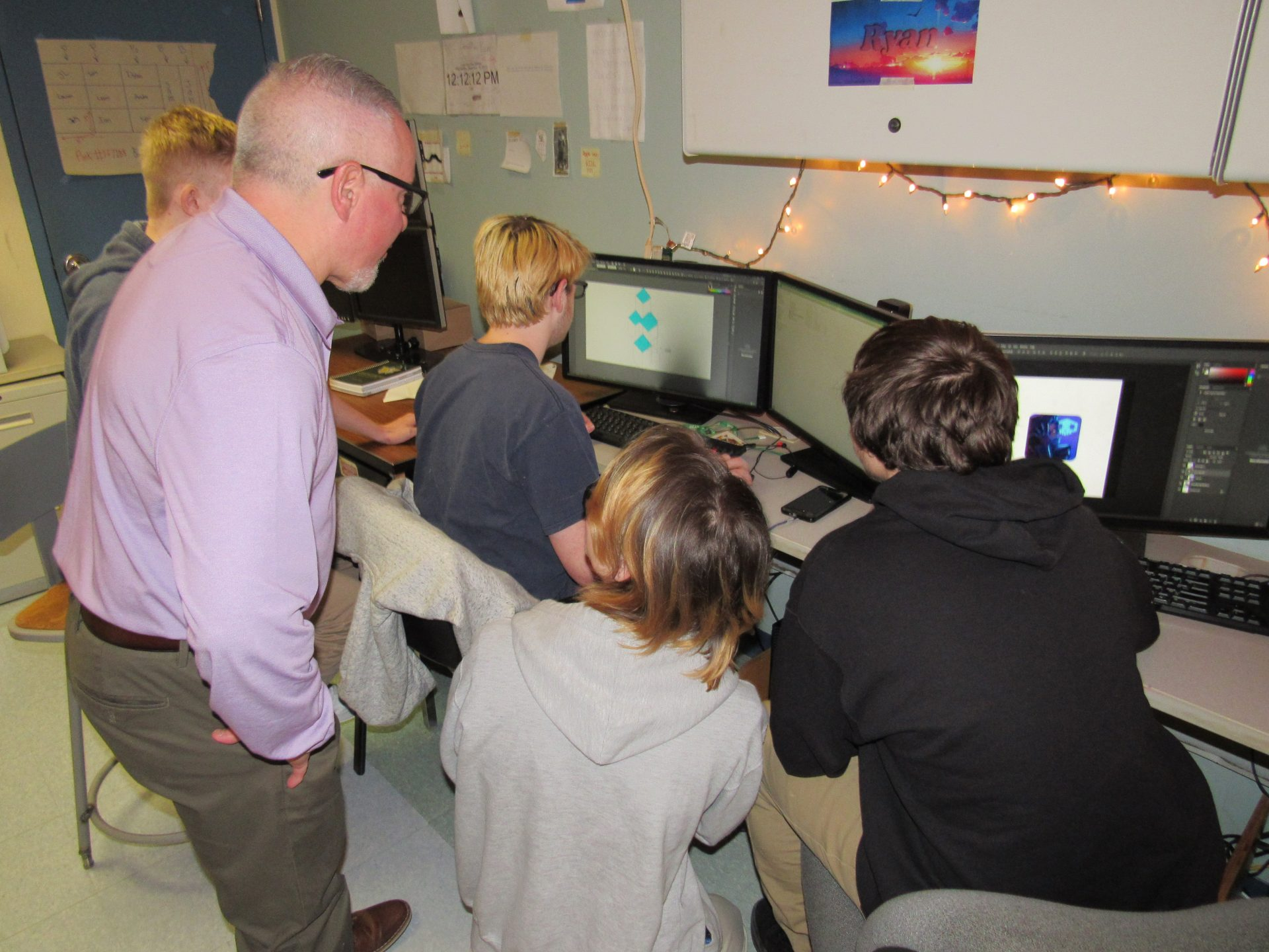 Info tech Teacher helping students