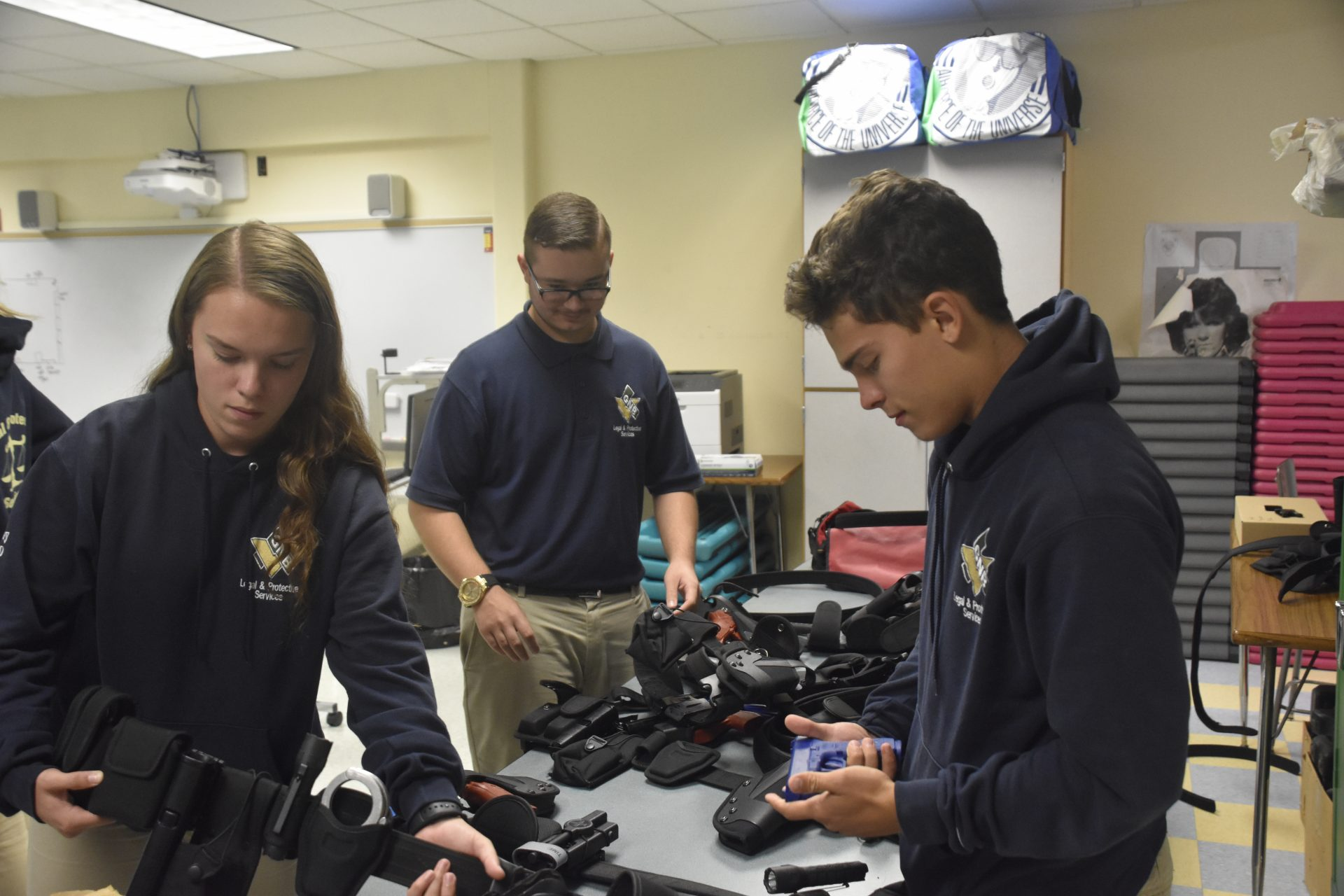 Three Students Looking Over Equipment