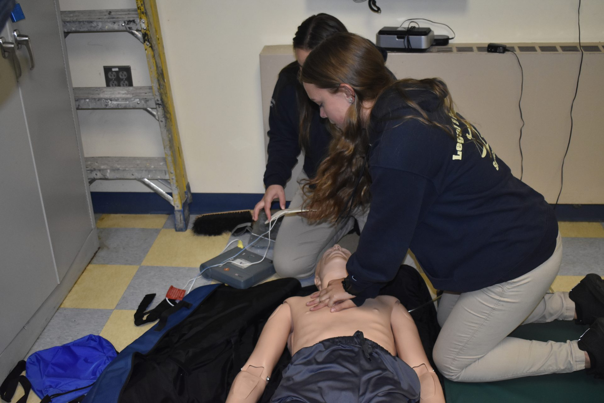 Students practicing CPR on dummy