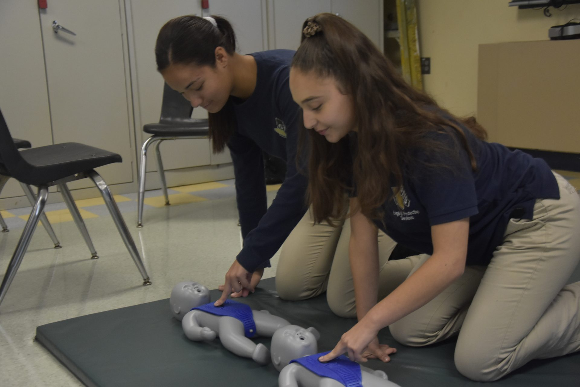 Students practicing CPR on baby dummies