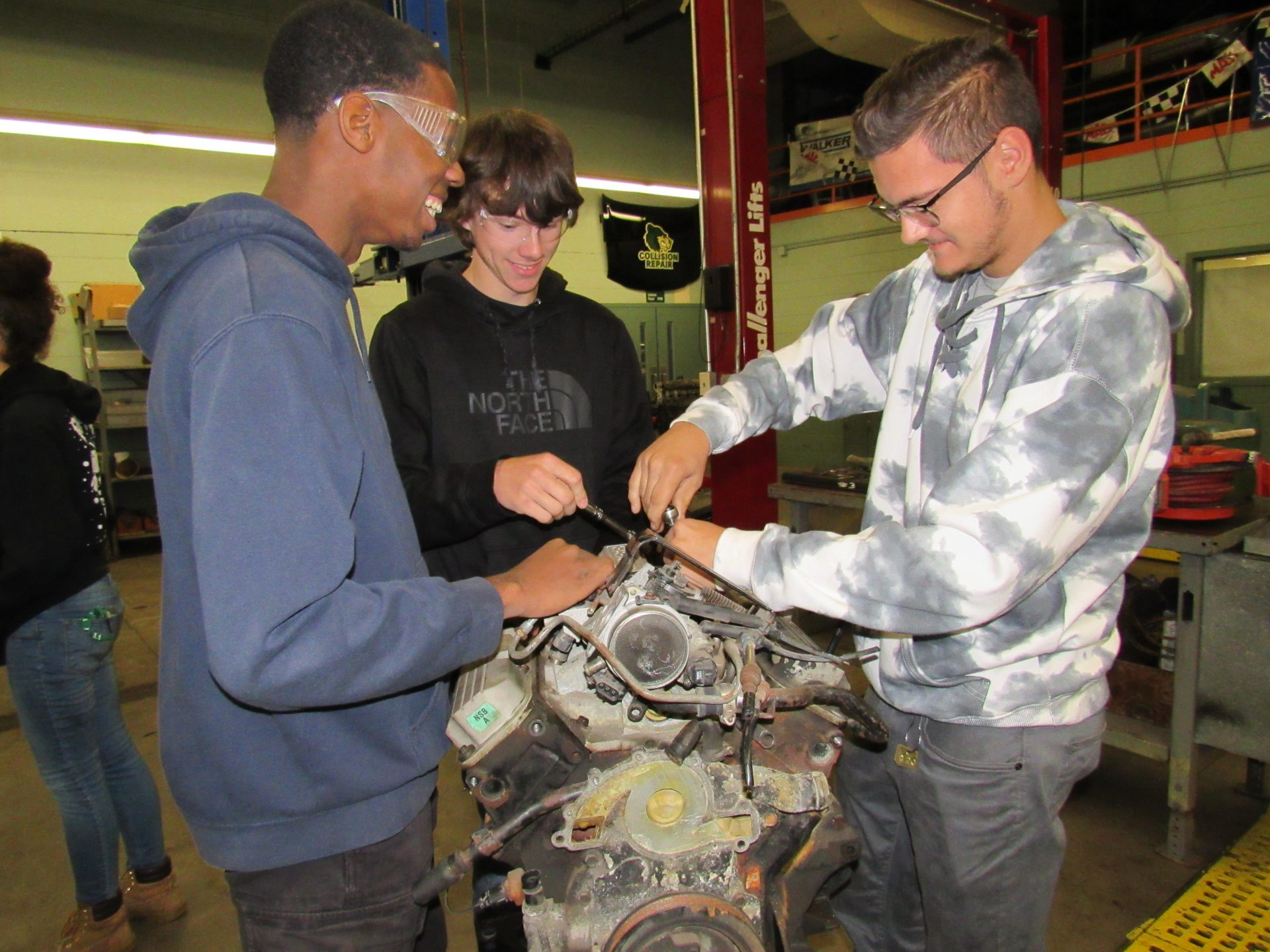 automotive students working on engine