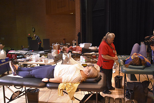 wide shot of three people donating blood for the blood drive