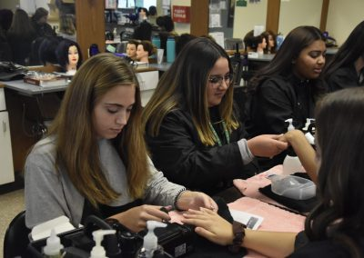 Three girls are seen working at a table on cosmetology related things