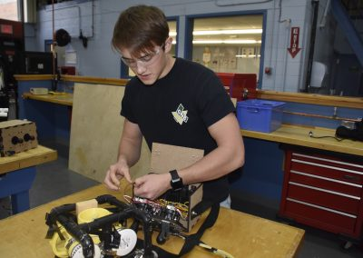 Jack working in shop on a machine.