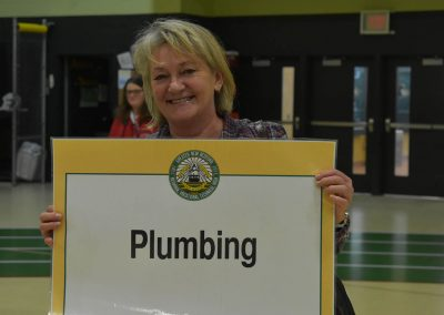 GNBVT Faculty Member Presenting Plumbing Category Sign