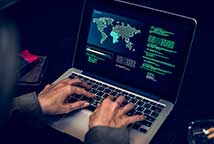 Stock photo of a man hacking on a computer