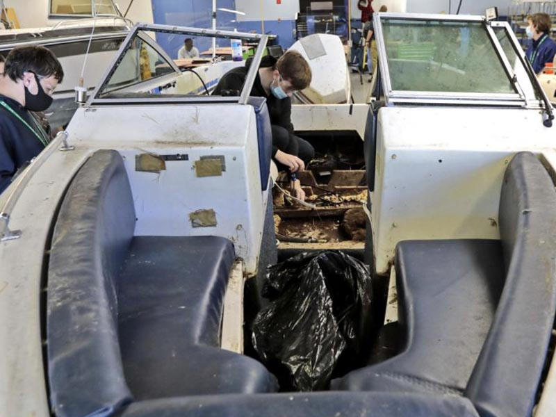 marine exploratory student scrapping boat properly