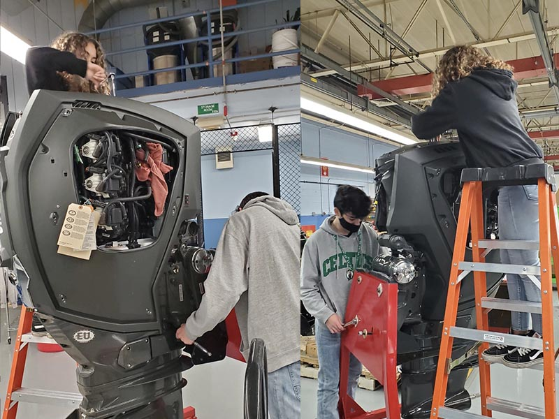 marine technology exploratory students working on an engine while on a ladder