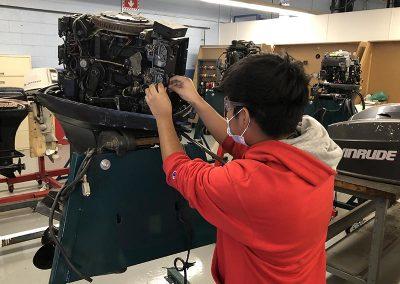 marine exploratory student working on an engine