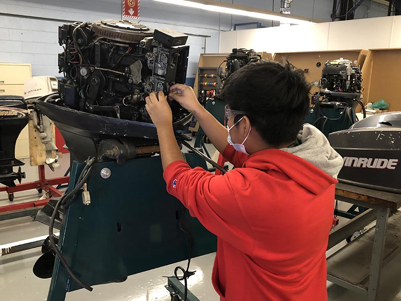 marine exploratory student working on an engine