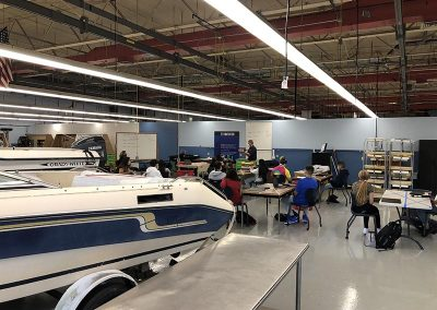 marine technology teacher presenting students a lesson with boat in background