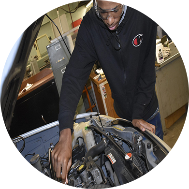 student working inside a cars engine